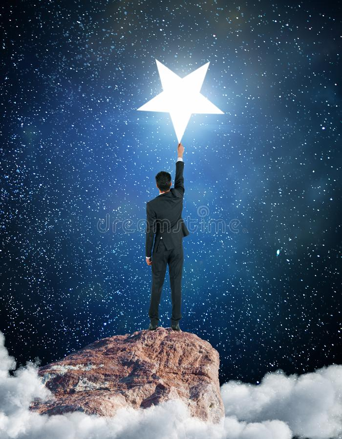 Aim concept. Back view of young businessman on cloudy mountain top reaching bright star. Aim concept stock image