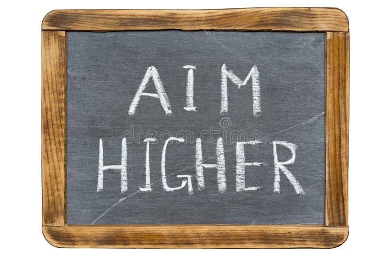 Aim higher. Slogan handwritten on vintage slate chalkboard isolated on white stock photography