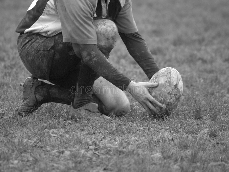 Aim for the post. Black & White image of a rugby player placing the ball on the ground for a conversion stock image