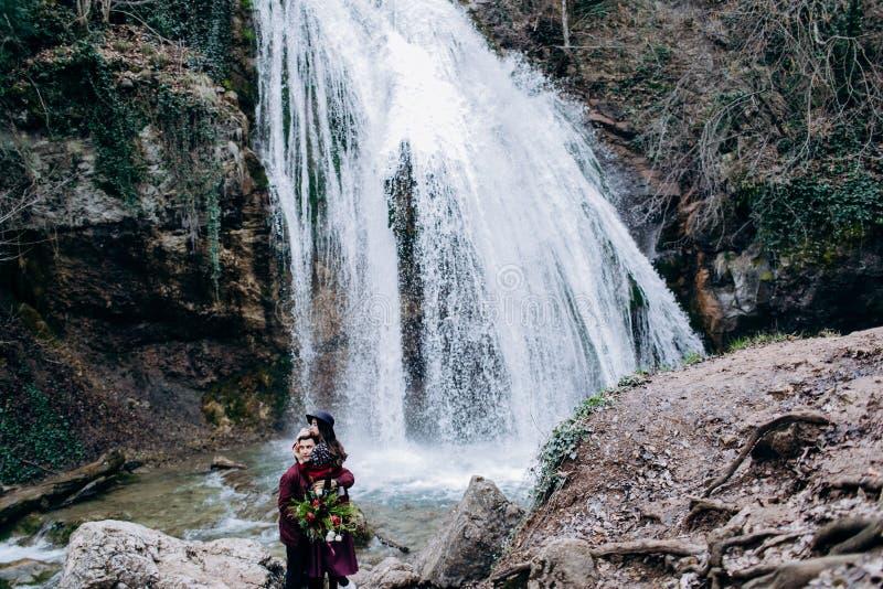 Aimer, couple élégant et jeune dans l'amour sur le fond d'une cascade photo stock