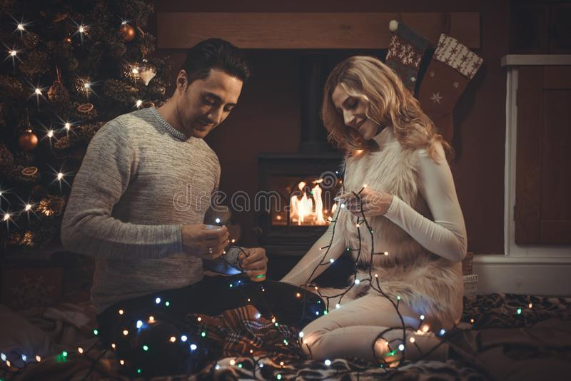 Aimer couplent par le feu de bois à Noël photographie stock libre de droits