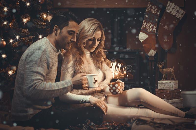 Aimer couplent par le feu de bois à Noël images libres de droits