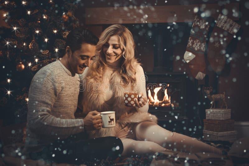 Aimer couplent par le feu de bois à Noël photos libres de droits