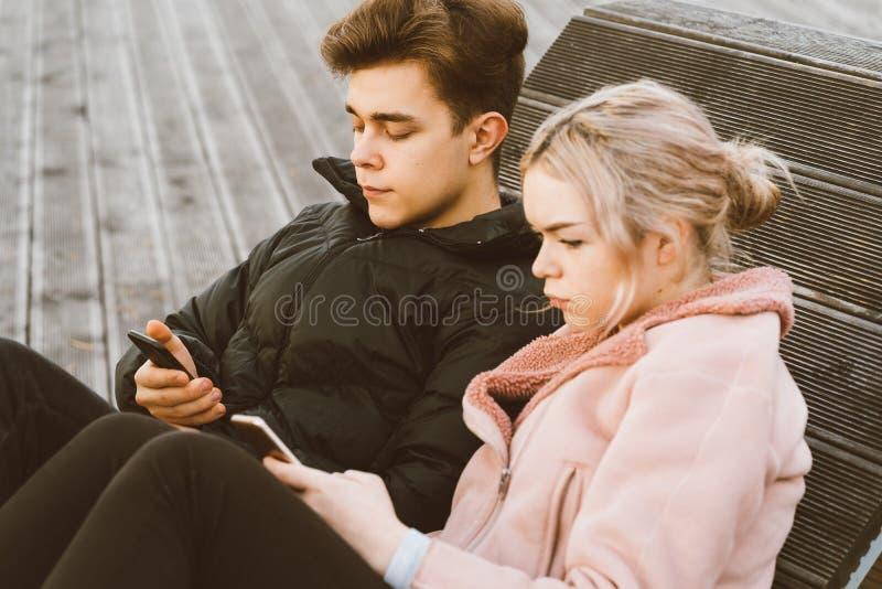 Aimer les adolescents, regardez les téléphones portables, asseyez-vous sur le banc du parc à l'automne Immersion dans le monde vi photographie stock libre de droits