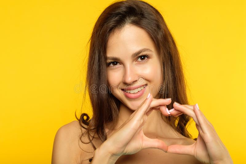 Aimez la fille de sourire d'émotion faisant le coeur pour former des mains photos libres de droits