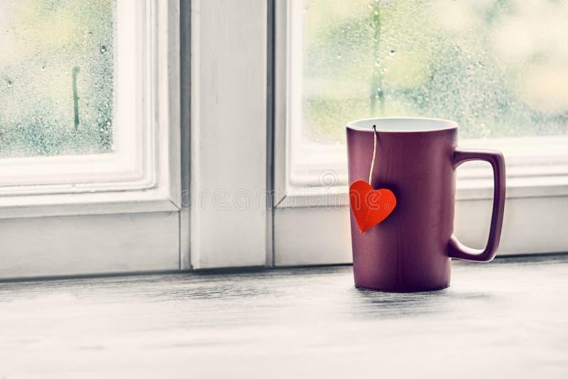 Aimez la tasse de coeur de thé sur un filon-couche lumineux de fenêtre photographie stock libre de droits
