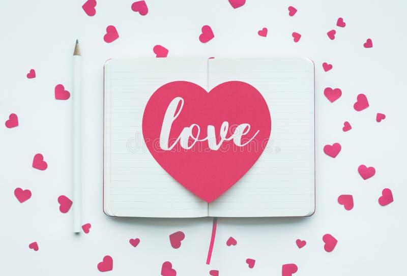 Aimez le message sur la forme rose de coeur sur le fond blanc de bloc-notes images libres de droits