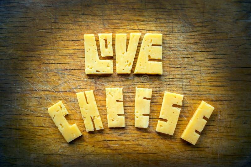 Aimez le mot des textes de fromage sur vieux le bois rayé de vintage par brun rustique photos libres de droits