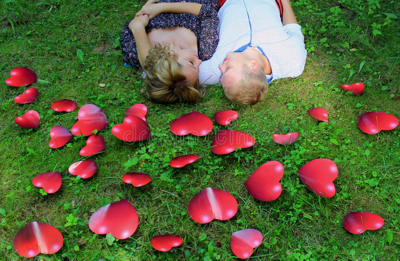 Aimez les jeunes couples détendant sur l'herbe parmi les coeurs rouges image libre de droits
