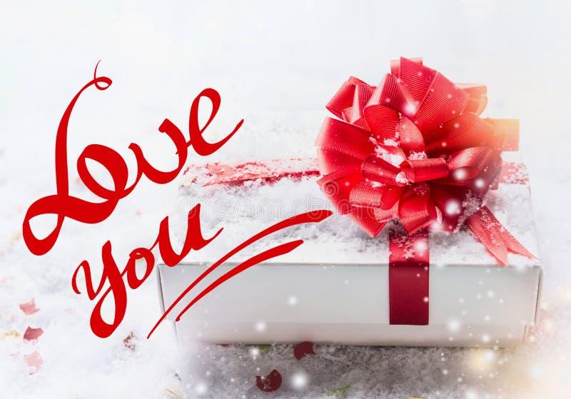 Aimez-vous lettrage des textes avec le boîte-cadeau blanc, arc rouge sur la neige avec le bokeh et chutes de neige Déclaration de photo libre de droits