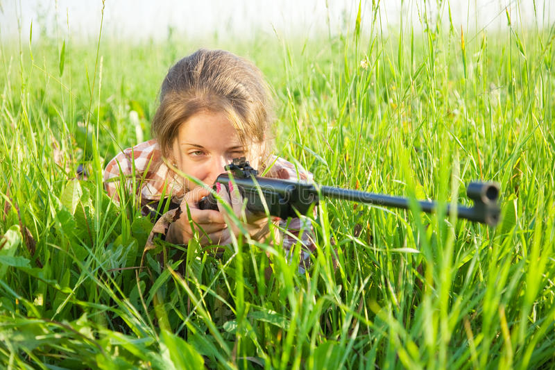 Aiming girl. Young girl aiming pneumatic air rifle outdoor royalty free stock images
