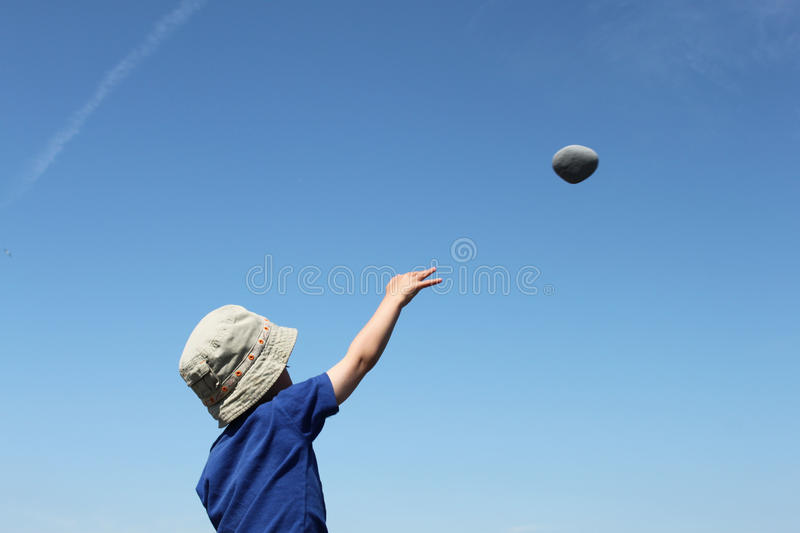 Aiming High. A litte boy throwing a stone up into a clear blue sky. Space for copy stock image