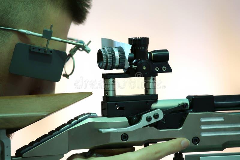 Aiming a pneumatic air rifle. Young man aiming a pneumatic air rifle royalty free stock images