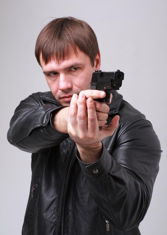 Aiming. Serious man with a gun. stock photography