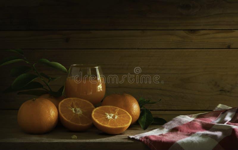 Ainda frutos da vida; Tanjerinas com vidro do suco fresco alaranjado imagem de stock
