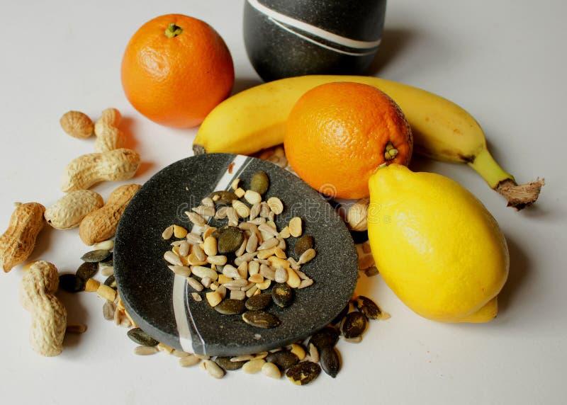 Ainda vida - bacias pretas com fruto fresco e as várias sementes fotos de stock