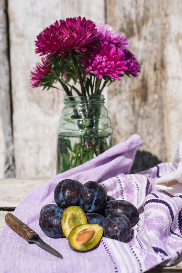 Ainda vida com ameixas e um ramalhete dos ásteres em um estilo rústico fotografia de stock royalty free