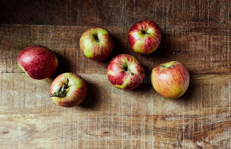Ainda vida com as maçãs outonais vermelhas na tabela de madeira rústica; visto de cima de fotos de stock royalty free