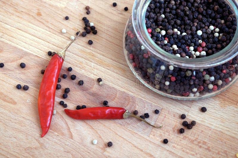 Ainda vida com as sementes da pimenta vermelha da paprika e da pimenta preta dentro do frasco de vidro redondo e dispersadas no f imagem de stock