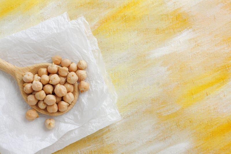 Ainda vida com as sementes do grão-de-bico no pano de madeira da colher e do papel fotografia de stock royalty free