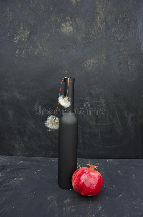 Ainda vida com as sementes pretas da garrafa, da romã e do dente-de-leão fotografia de stock
