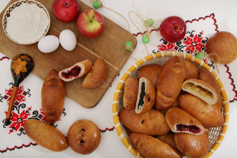 Ainda-vida com as tortas tradicionais do russo, ingredientes - farinha, ovos, maçãs Na toalha de mesa autêntica com uma colher de fotografia de stock royalty free
