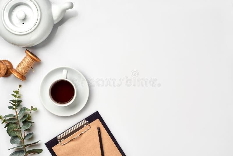 Ainda vida com copo de chá e os índices de um espaço de trabalho composto Objetos diferentes na tabela branca Configuração lisa imagens de stock royalty free