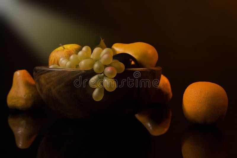 Ainda-vida com fruta em um prato de madeira fotos de stock royalty free
