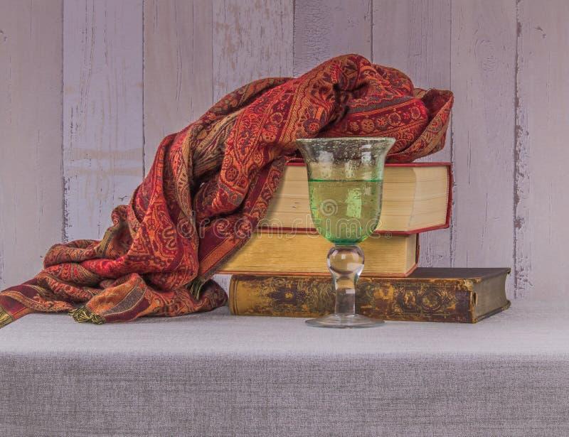 Ainda vida com livros velhos, um vidro da água potável e um luxur fotografia de stock royalty free