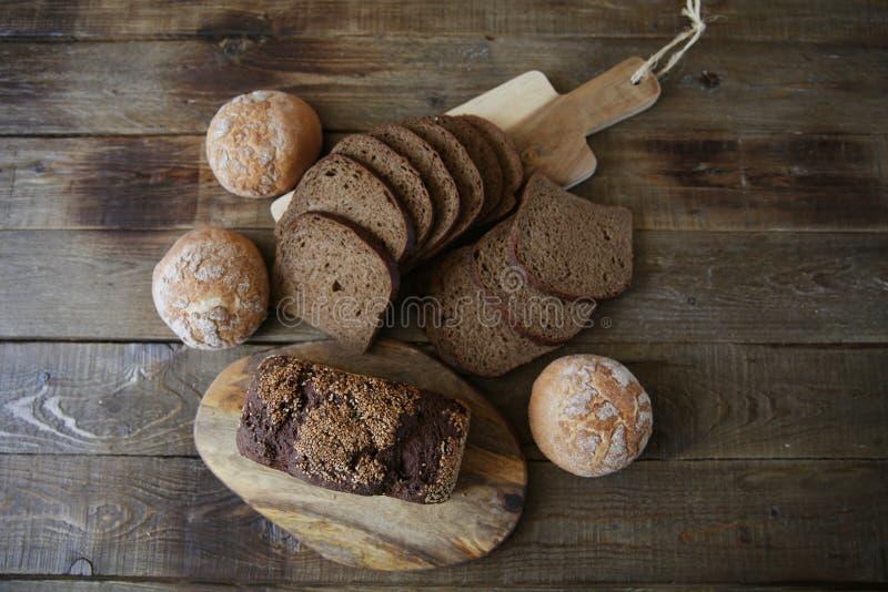 Ainda vida com pão de centeio com sementes de sésamo e pão branco em um fundo rústico de madeira, vista superior dos bolos, confi imagens de stock royalty free