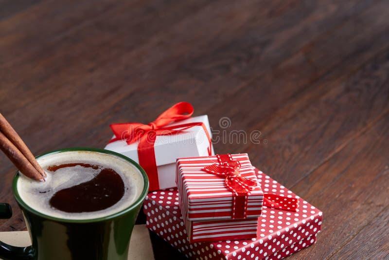 Ainda vida com presente de época natalícia da xícara de café na caixa de cor vermelha pequena com fita e curva no fundo de madeir fotografia de stock royalty free