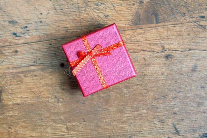 Ainda vida com presente de época natalícia na caixa de cor vermelha pequena, coberta com a fita com curva na opinião superior do  fotografia de stock royalty free