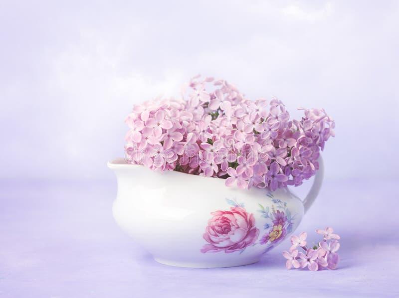 Ainda vida com ramo pequeno do lilás no barco de molho velho da porcelana na luz - fundo violeta imagens de stock royalty free