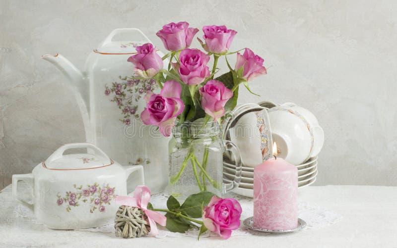 Ainda vida com rosas e pratos imagens de stock royalty free