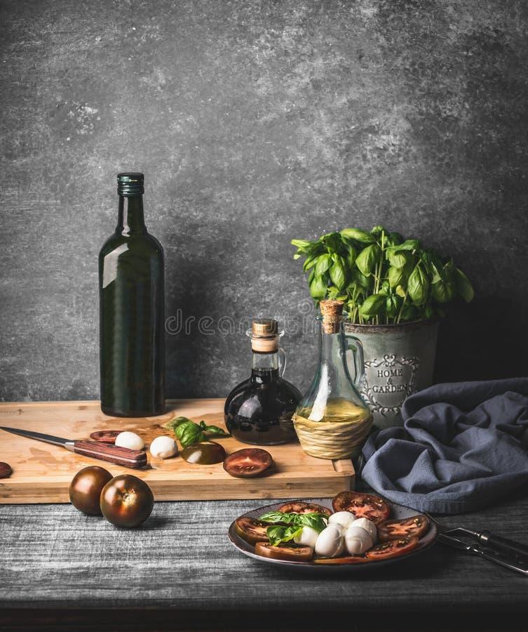 Ainda vida com a salada caprese italiana servida na tabela rústica com as ervas em pasta da cozinha da manjericão e a garrafa do  foto de stock