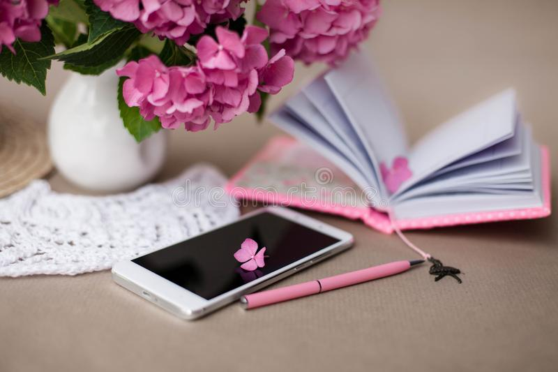 Ainda vida com telefone celular, flores da hortênsia, o caderno fêmea aberto e a pena cor-de-rosa fotos de stock royalty free