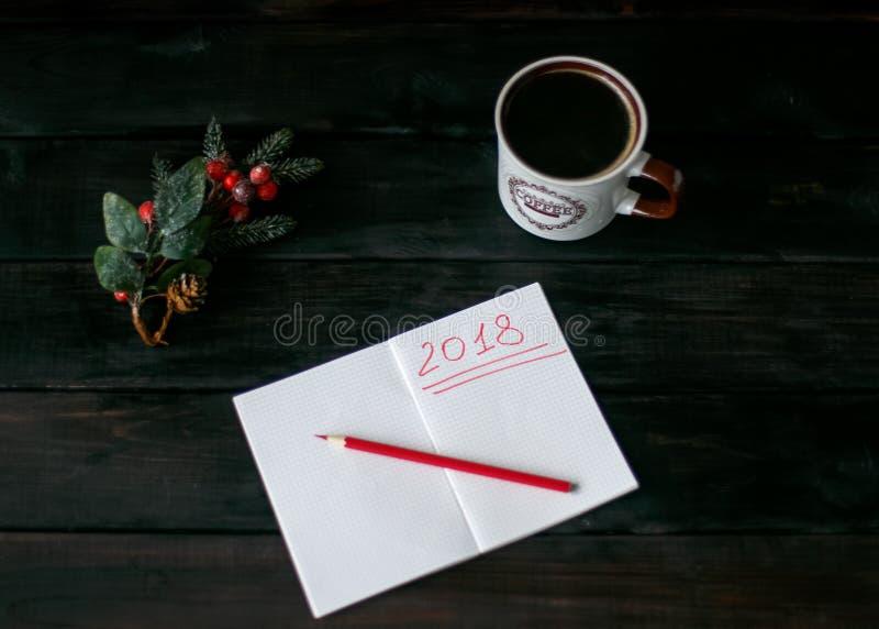 Ainda-vida com um caderno com uma inscrição vermelha 2018, uma xícara de café imagem de stock