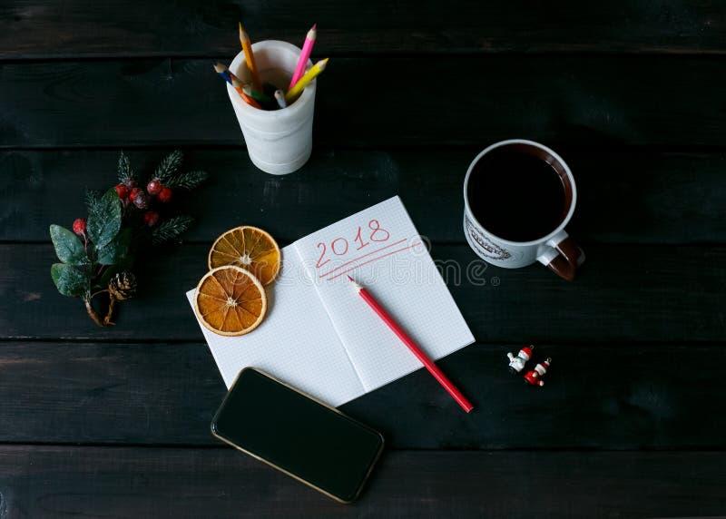 Ainda-vida com um caderno com uma inscrição vermelha 2018, uma xícara de café fotos de stock