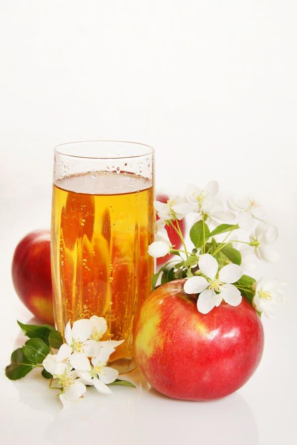 Ainda vida com um vidro do suco fresco e de maçãs vermelhas maduras foto de stock royalty free