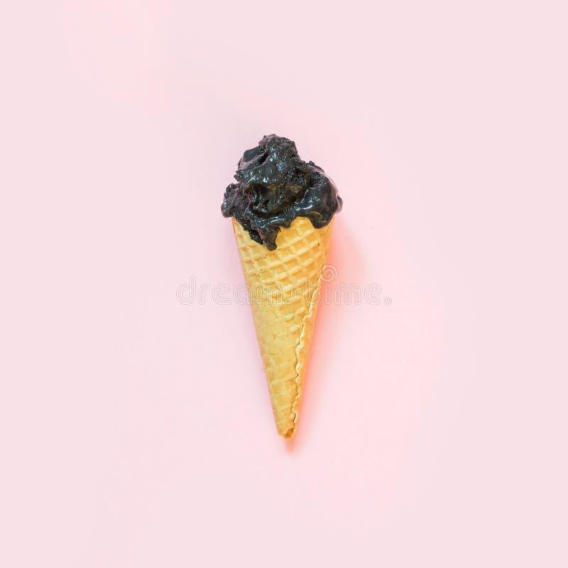Ainda vida criativa do gelado preto no cone do waffle no fundo cor-de-rosa Conceito da mola Vista superior imagem de stock royalty free