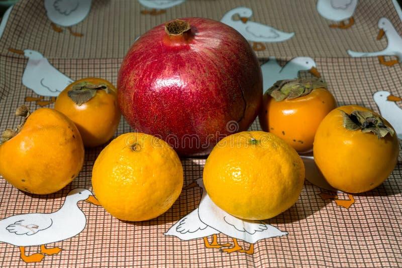 Ainda-vida da cozinha Frutos maduros integrais da romã, do mandarino e do caqui em uma toalha de mesa bonito imagens de stock royalty free