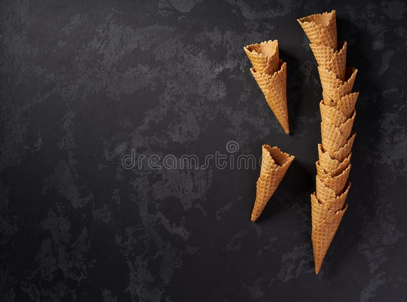 Ainda-vida da torre empilhada de cones de gelado vazios do waffle no fundo escuro, vista superior fotos de stock
