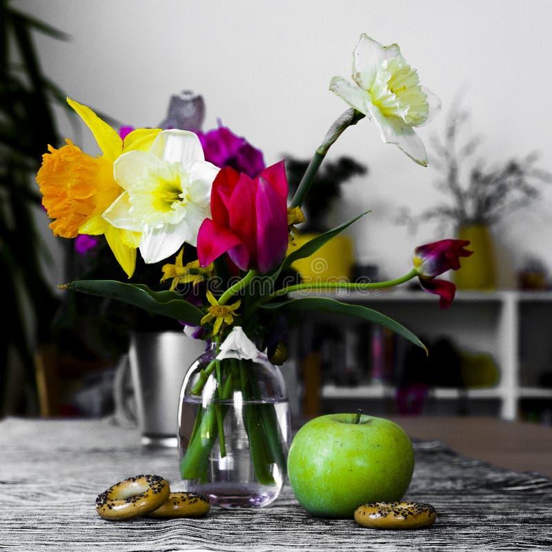 Ainda vida das flores em um vaso, na composição das tulipas e em narcisos amarelos com Apple fotos de stock royalty free