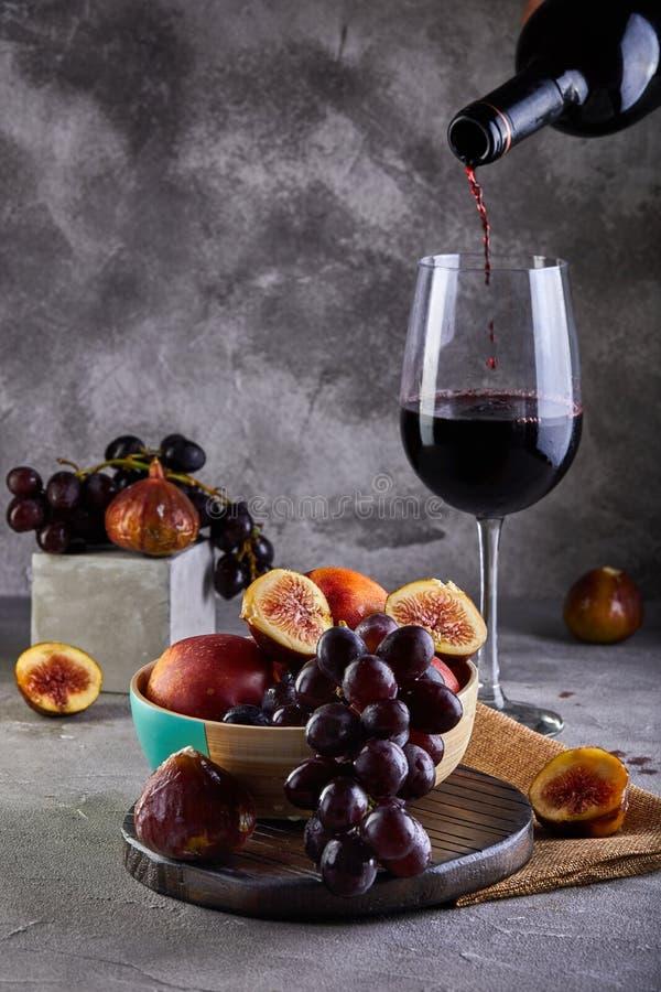 Ainda vida das uvas, dos pêssegos, dos figos e dos vidros do vinho tinto em um cinza fotografia de stock