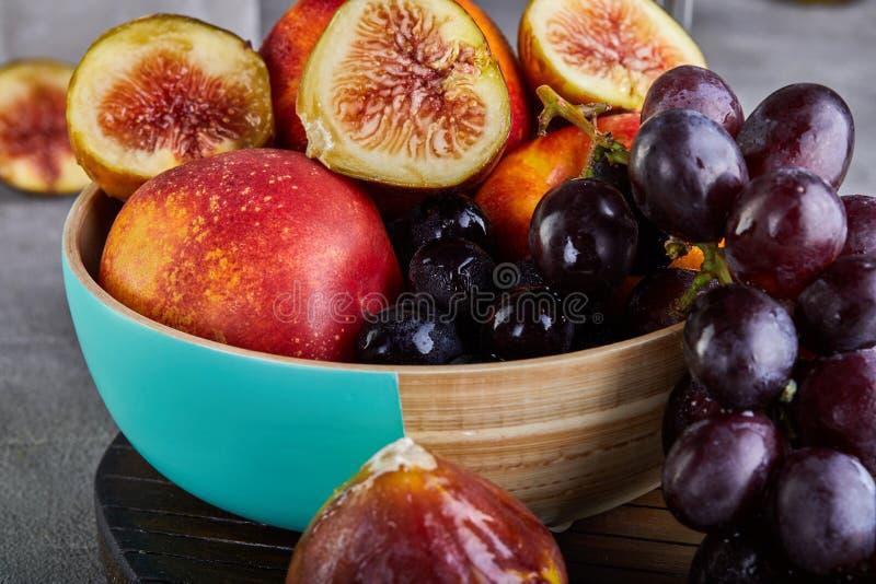 Ainda vida das uvas, pêssegos, figos em um fundo cinzento imagens de stock