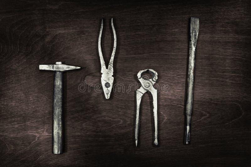 Ainda a vida de ferramentas da construção martela, alicates, tenazes de brasa, bocado de broca em uma placa de madeira escura fotografia de stock
