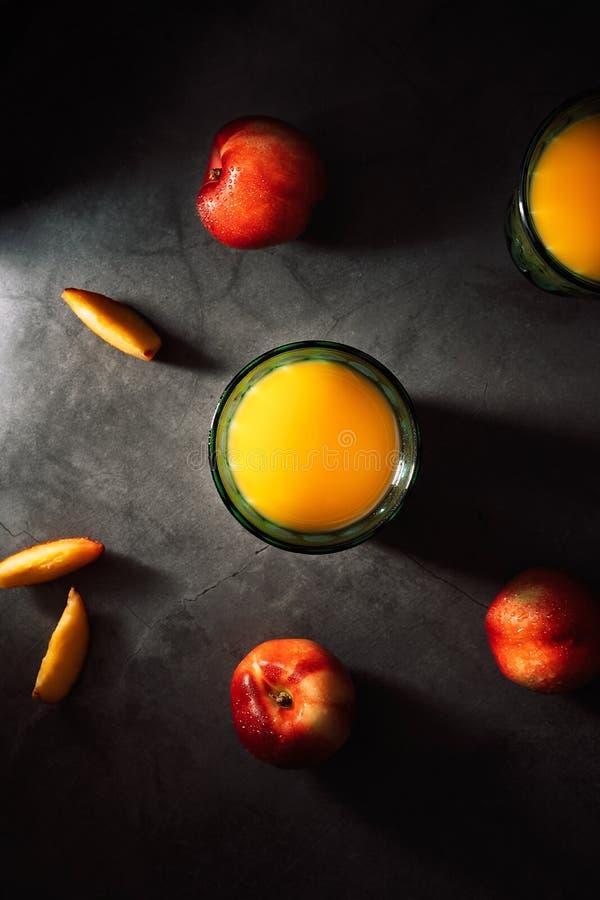 Ainda vida de nectarina frescas com gotas da água e do suco em vidros do vintage de turquesa no fundo escuro Baixa chave foto de stock