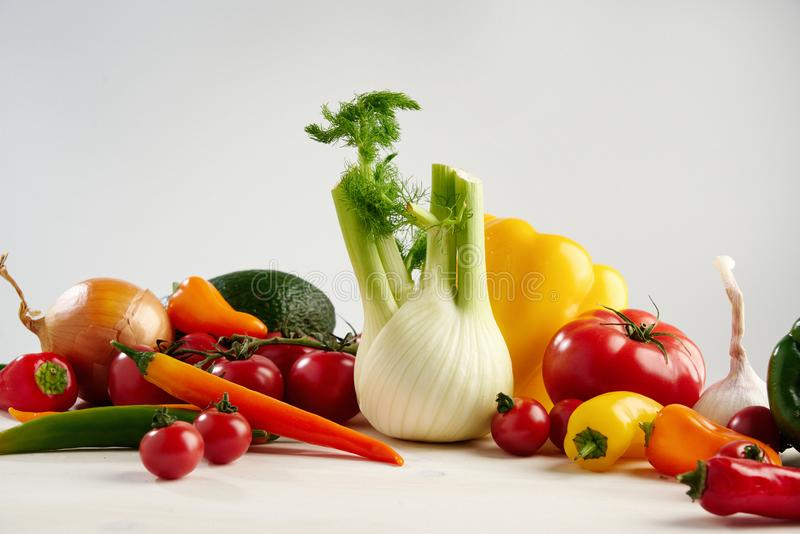 Ainda vida de vegetais verdes sazonais diferentes frescos abacate de um grupo, erva-doce, alho, cebola, tomate, pimenta amarela v fotografia de stock