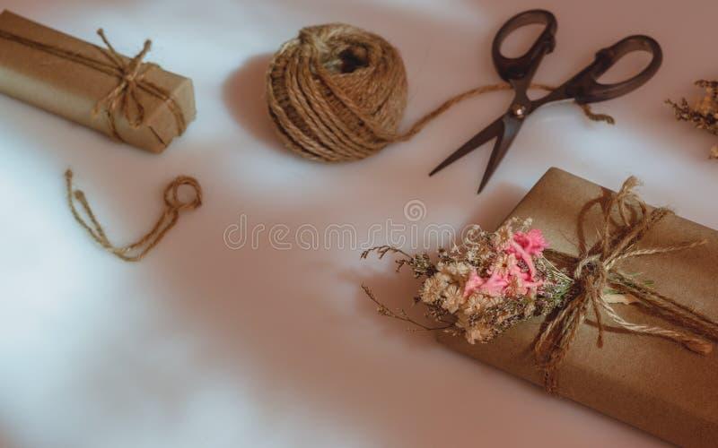 Ainda vida disparada da caixa de presente feito a mão pequena bonita de DIY & do x28; package& x29; com flores e corda decorativa fotos de stock royalty free