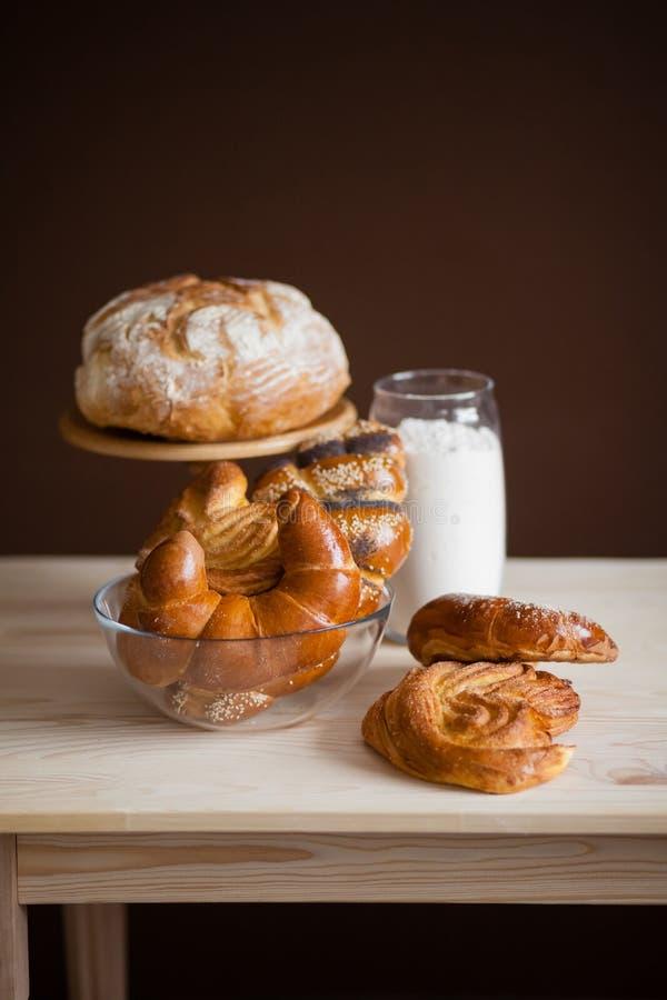 Ainda vida dos rolos, do pão, do baguette e da farinha em uma tabela imagem de stock royalty free